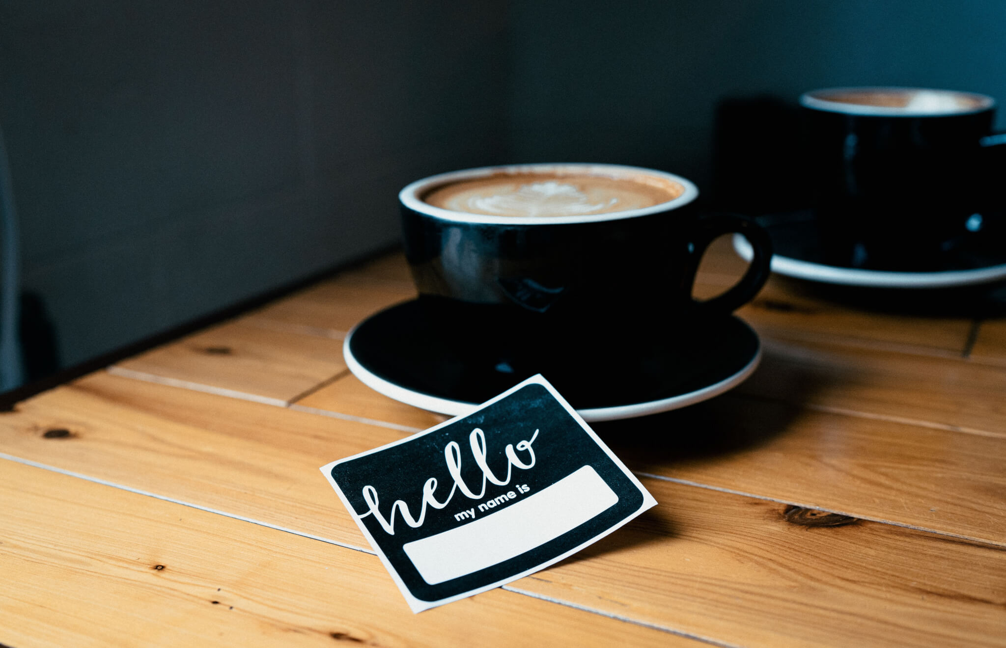 Cup of coffee and a name tag on a table